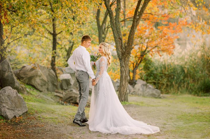 Groom affectionately looks at the bride in a gray steep wedding expensive dress with a long train, gently holds her hand. Stand together in forest with green stock photography