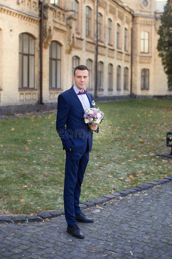 The Groom In A Blue Suit And Bow Tie Posing In The Photo Stock ...