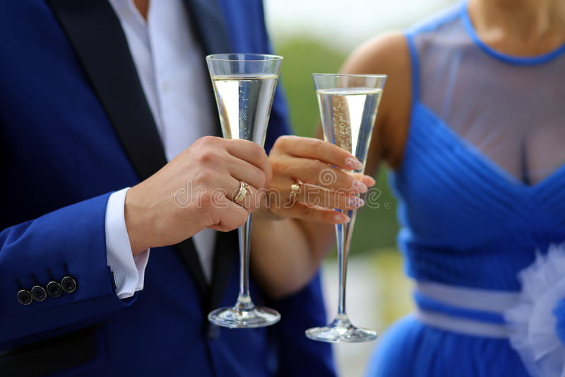 The groom in a blue suit and the bride in a blue dress standing with glasses in which is poured the champagne stock image