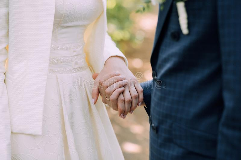 The groom in a blue suit and the bride in a wedding dress hold each others hands. Hands close up royalty free stock photos
