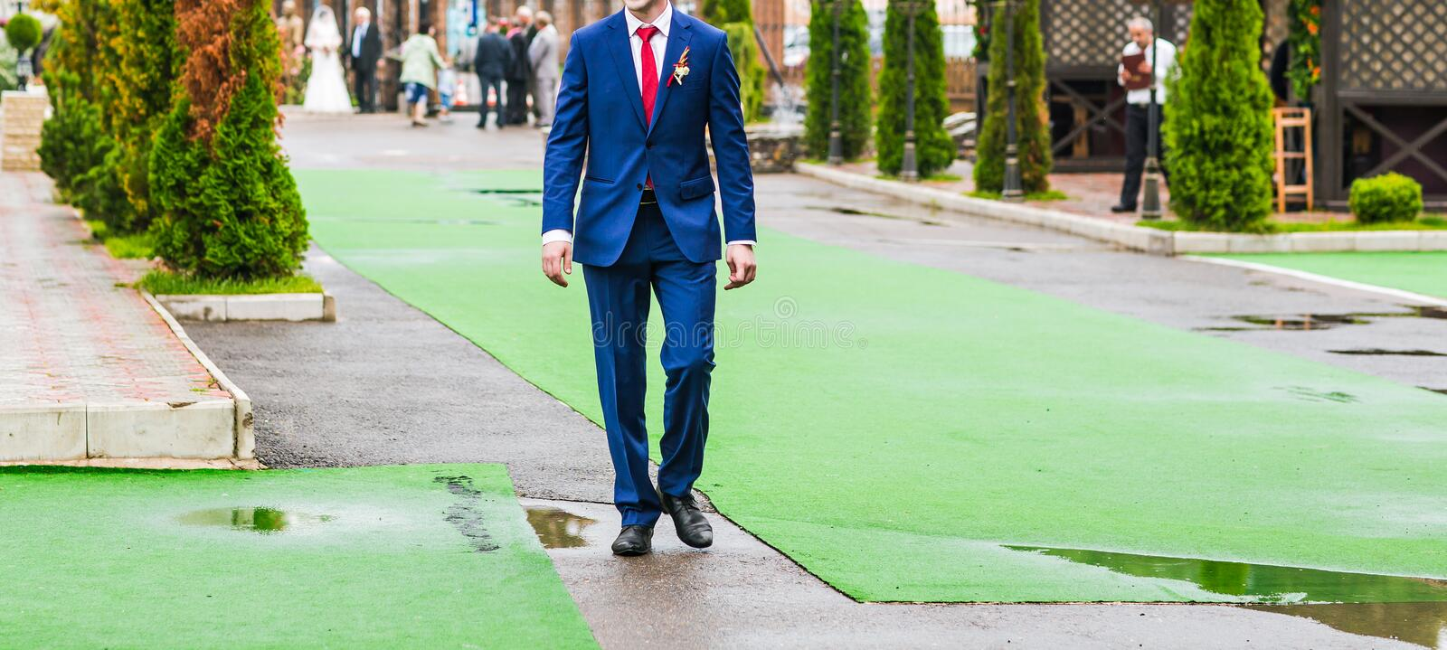 Groom in blue suit is on the green track at. Joyful happy groom in blue suit is on the green track at wedding ceremony stock images