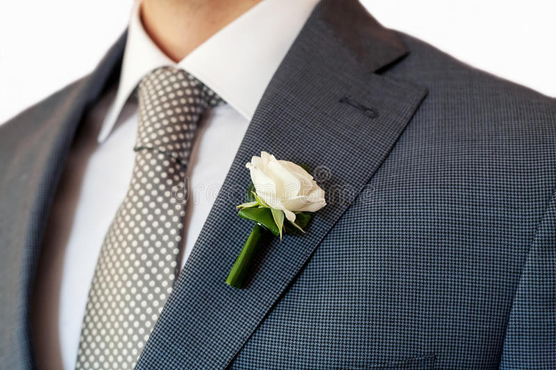 Groom boutonniere. Rose boutonniere in tuxedo lapel royalty free stock images