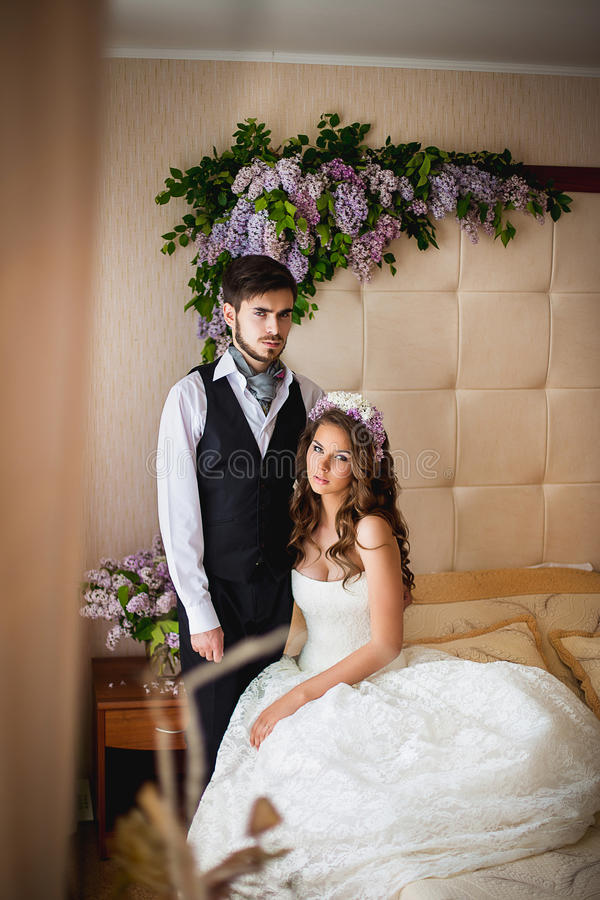 The groom and the bride on a bed. The groom with the bride sit on a bed. Nearby there are a lot of flowers of a lilac stock photos