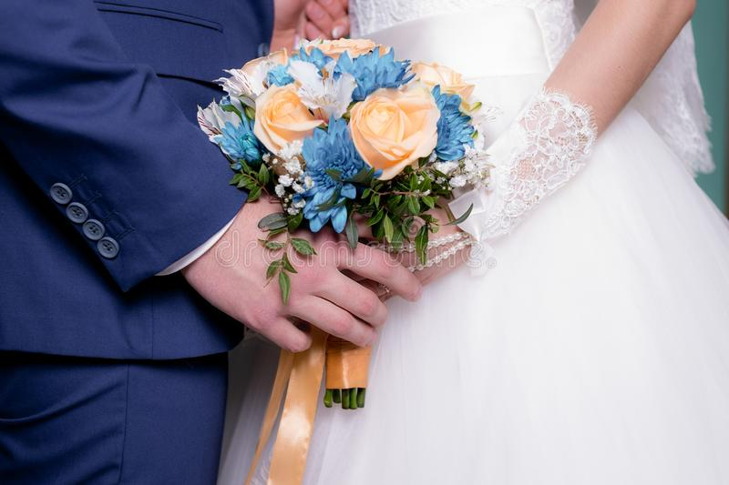 Groom with the bride, the bride`s bouquet, the bride is holding a bouquet, the bridegroom embraces the bride royalty free stock images