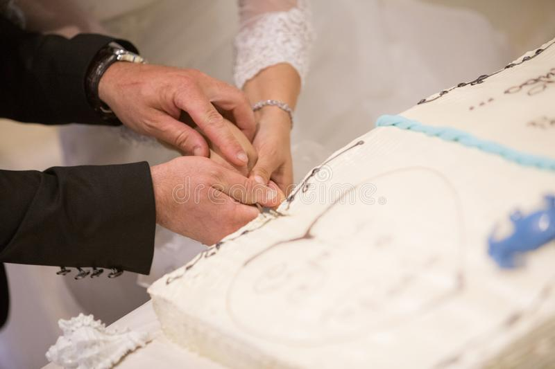 Groom and bride cutting the wedding cake royalty free stock photography