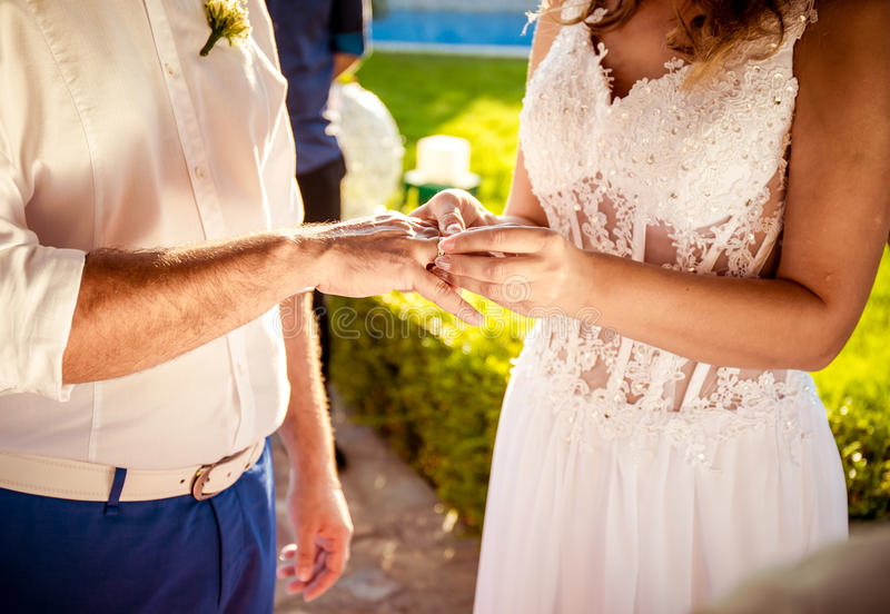 Groom and bride hands with wedding rings stock photos