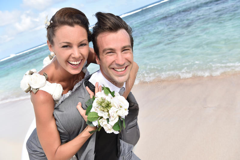 Groom and bride having fun on the beach stock photography