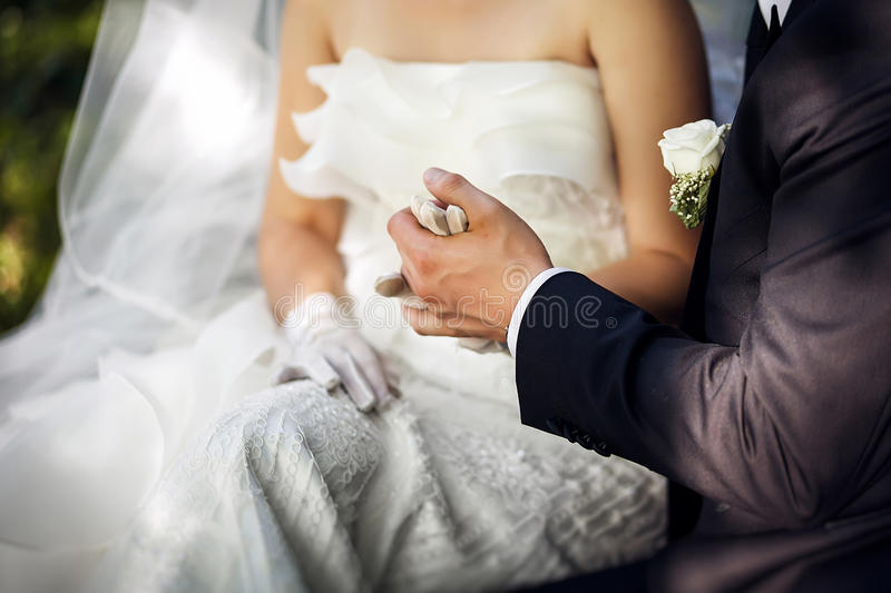 Groom and bride holding each others hands stock photography