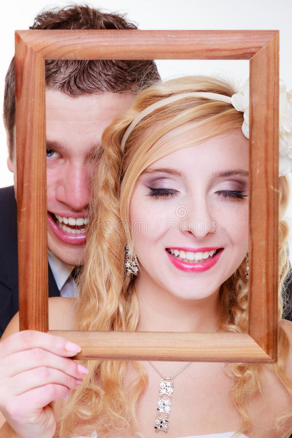 Groom and bride holding empty frame. Wedding day, positive relationship concept. Groom and bride holding, posing with empty photo frame royalty free stock image