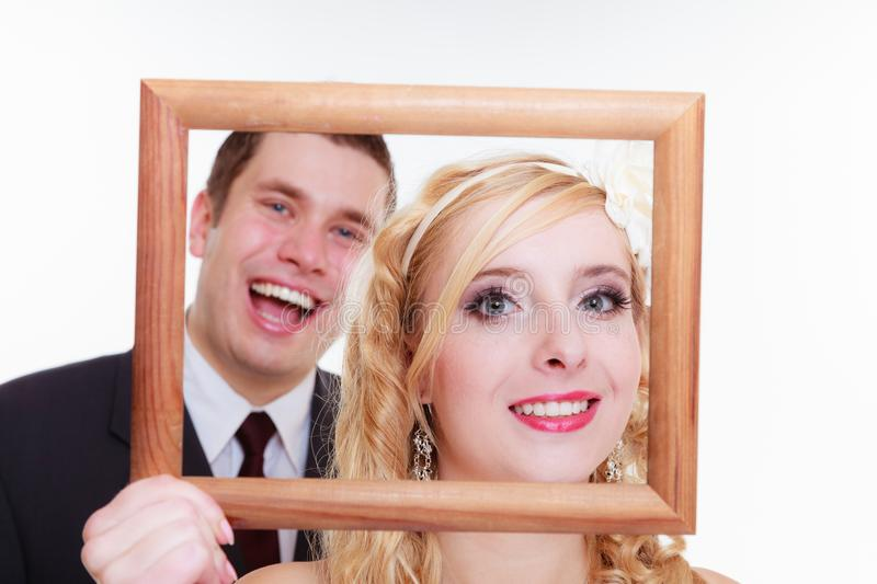 Groom and bride holding empty frame. Wedding day, positive relationship concept. Groom and bride holding, posing with empty photo frame stock photography