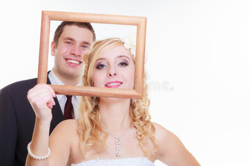 Groom and bride holding empty frame. Wedding day, positive relationship concept. Groom and bride holding, posing with empty photo frame royalty free stock images