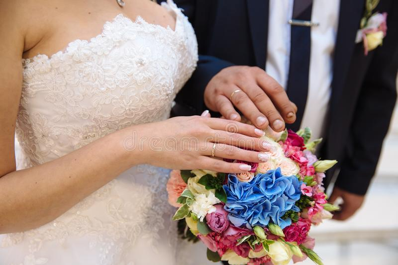Closeup groom and bride are holding hands at wedding day ang show rings. Concept of love family. Groom and bride are holding hands at wedding day stock photo
