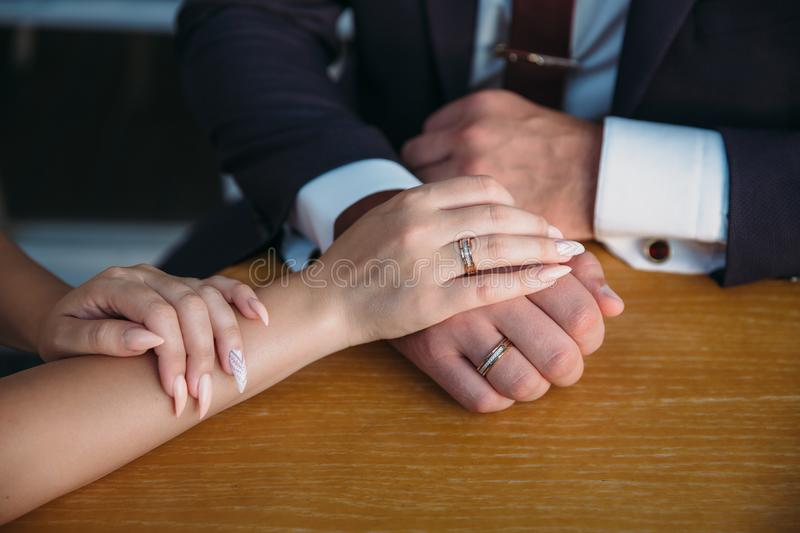 Closeup groom and bride are holding hands at wedding day ang show rings. Concept of love family. Groom and bride are holding hands at wedding day royalty free stock photo