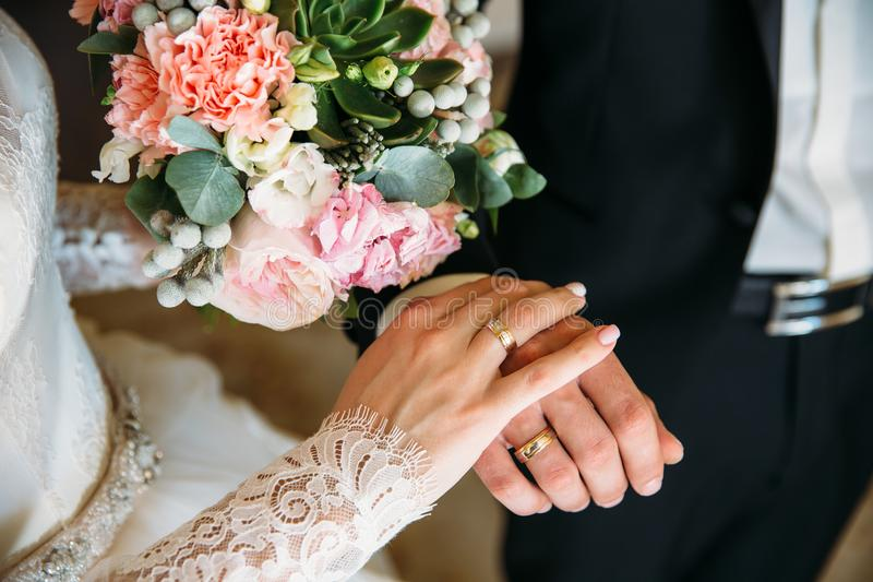 Closeup groom and bride are holding hands at wedding day ang show rings. Concept of love family. Groom and bride are holding hands at wedding day stock image