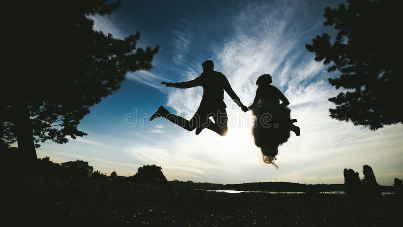 Groom and bride jumping against the beautiful sky. Silhouettes royalty free stock photography