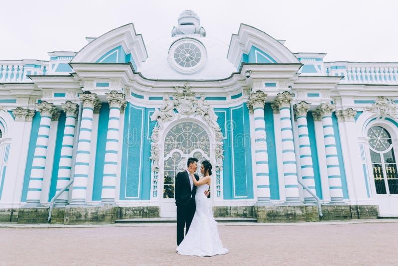 Groom and bride. Kiss near Wedding palace stock photos