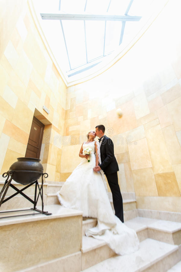 Groom and bride kiss standing on a white stairs under glass ceiling stock photography