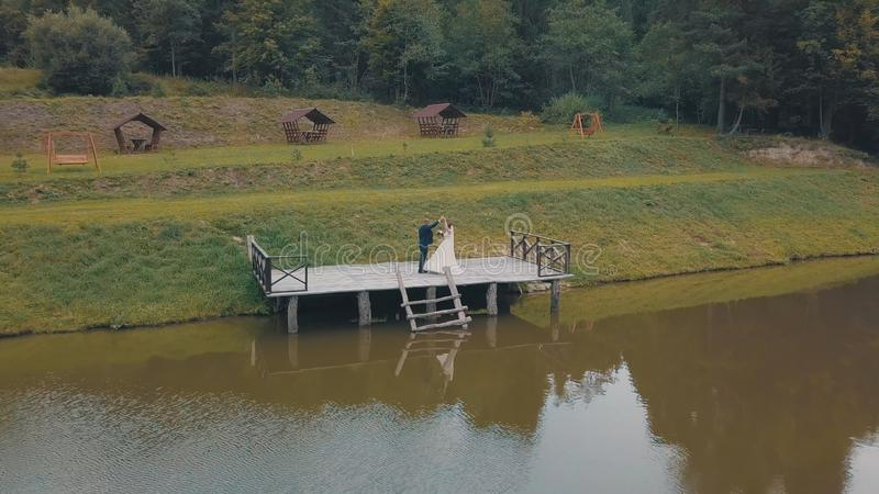 Groom with bride near lake in the park. Wedding couple. Aerial shot stock image