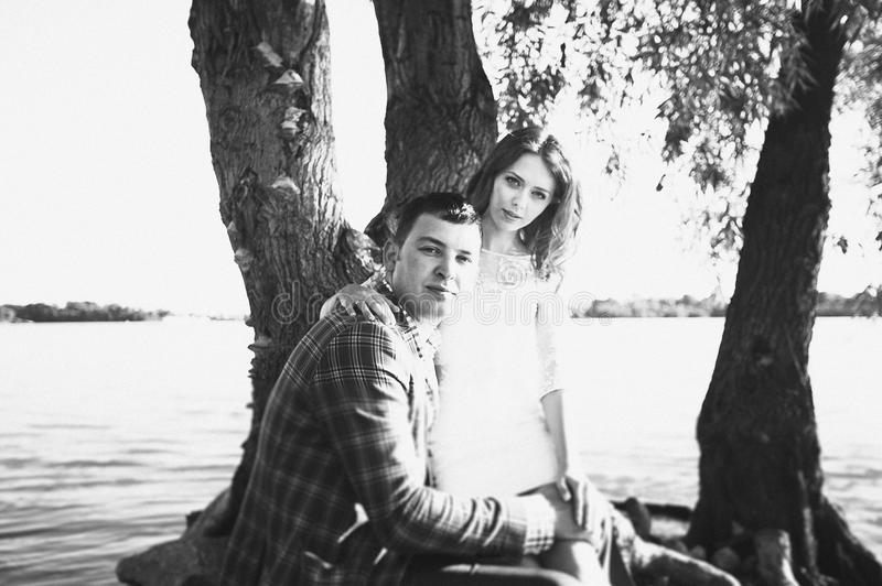 The groom and the bride on the river bank royalty free stock image