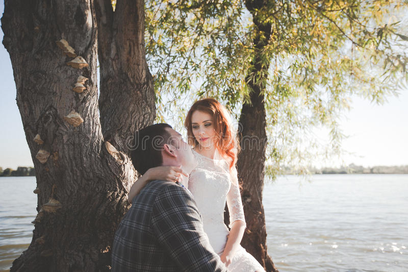 The groom and the bride on the river bank stock photography