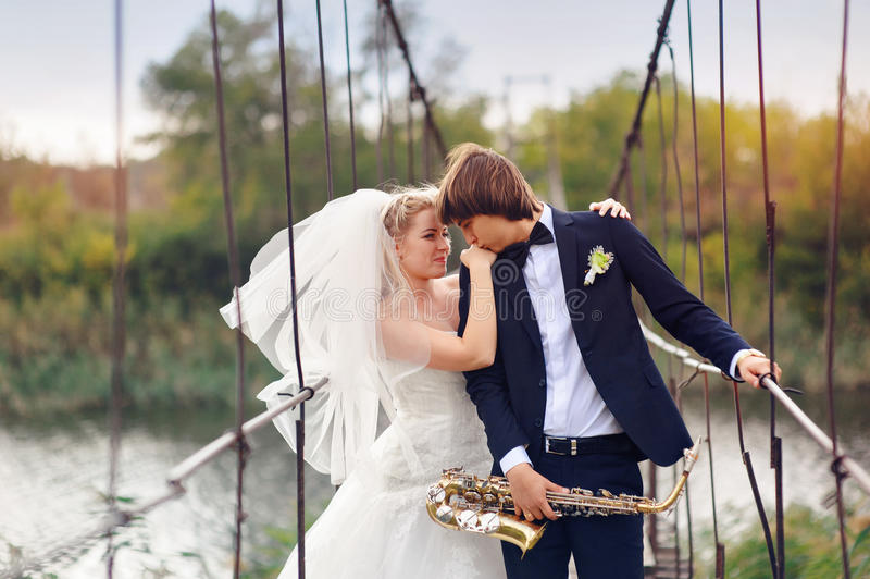 Groom and bride with sax bridge stock photography
