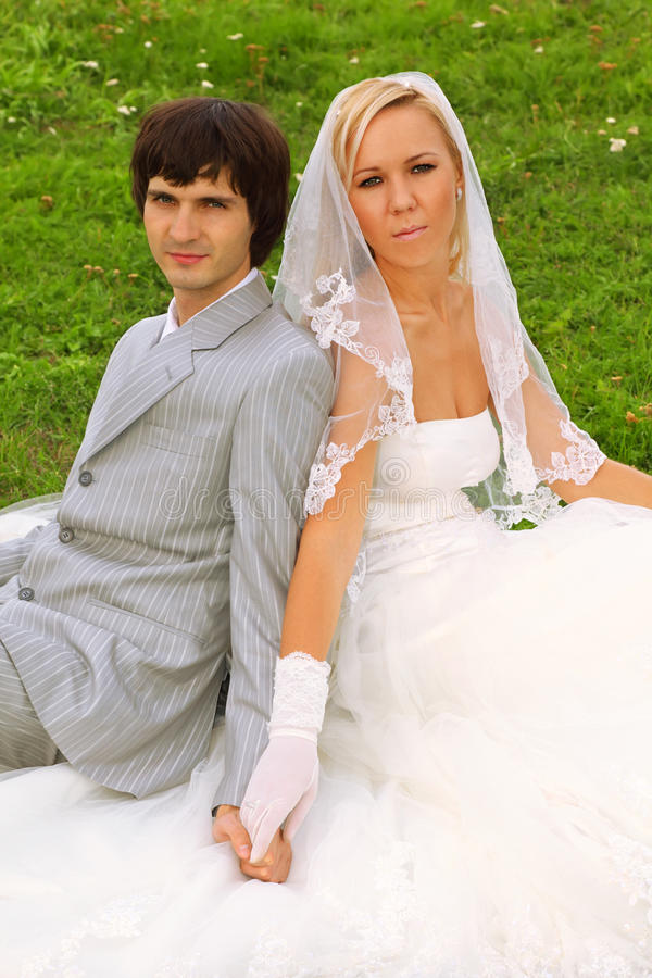 Groom and bride sitting on green grass royalty free stock photo
