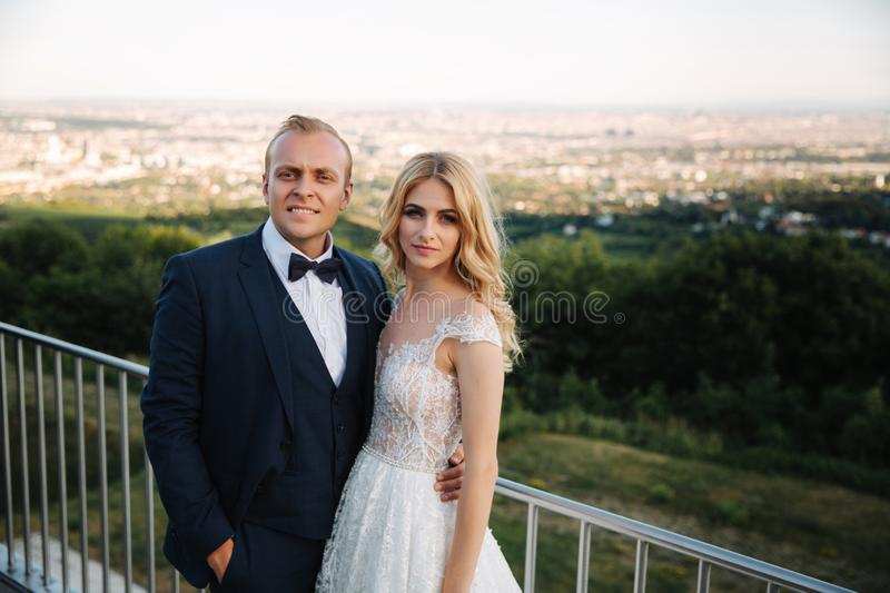 Groom and bride stand on the background of the city and drink champagne from wineglass. Clink glasses royalty free stock photos