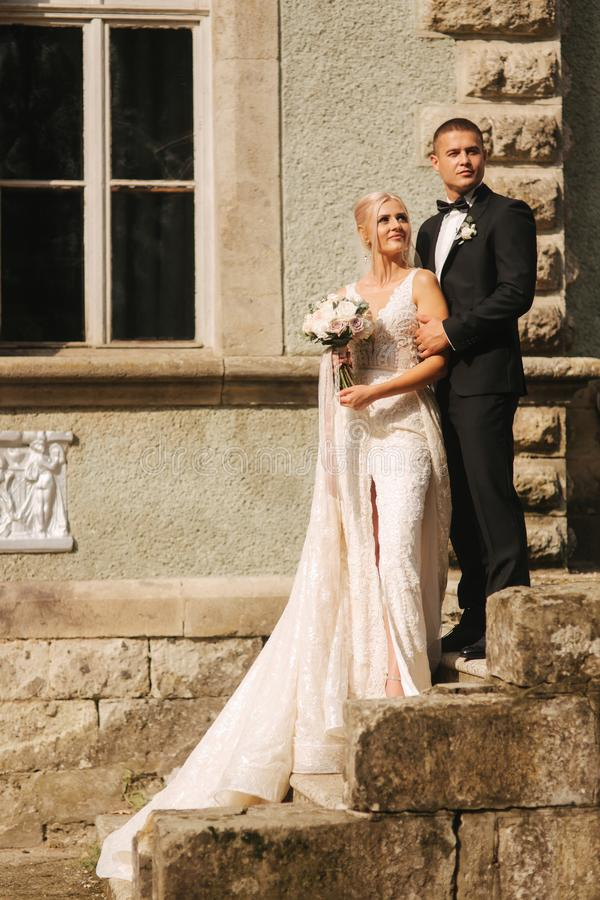 Groom and bride stand on stairs. Fashion model in elegant clothes. White long dress and stylish suit stock photo