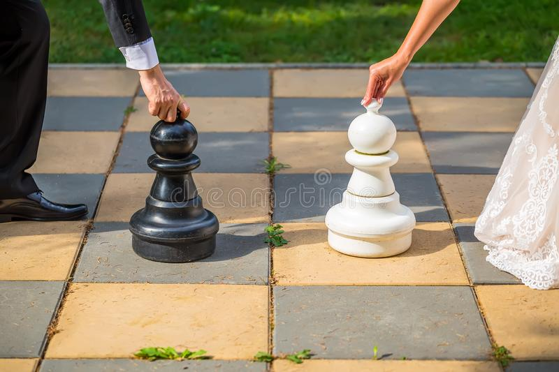 Groom and bride together on wedding day playing outdoor chess. royalty free stock images