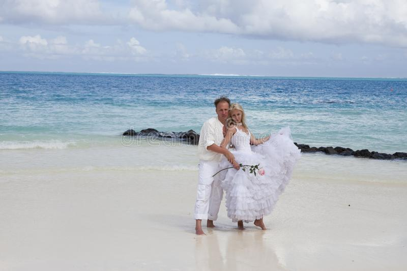 The groom and the bride on the tropical beach royalty free stock photography