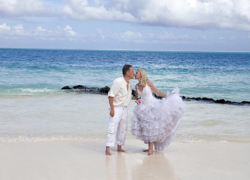 The groom and the bride on the tropical beach stock photography