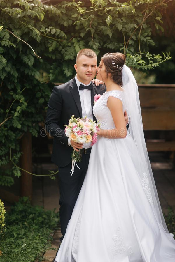 Groom and bride walk in the park on their wedding day. Happy couple spend time together royalty free stock images
