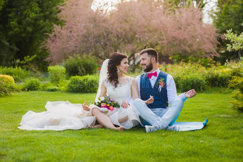 Groom and bride in yoga lotus pose in garden royalty free stock photo