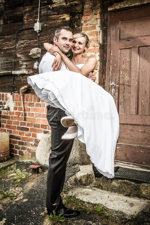 The groom brings the bride to the house royalty free stock photo