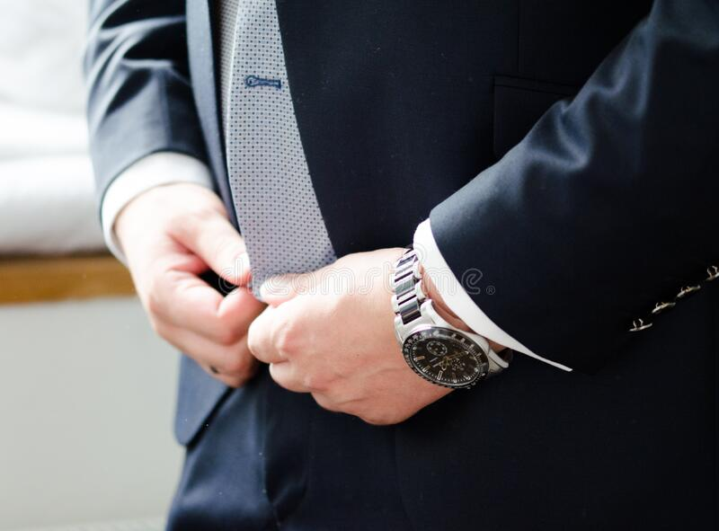 Groom buttoning his tuxedo royalty free stock photo