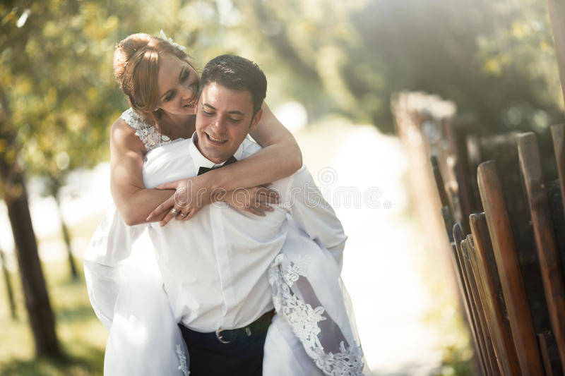 Groom carrying bride piggyback royalty free stock images
