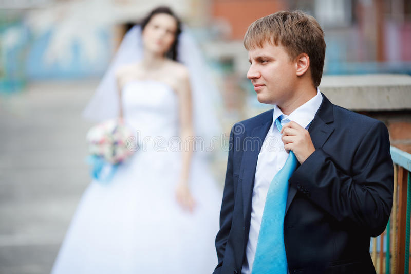 The groom dark blue suit straightens turquoise tie. With a sour face, in the background tired and frustrated bride waiting. The concept of long wait before the stock photos