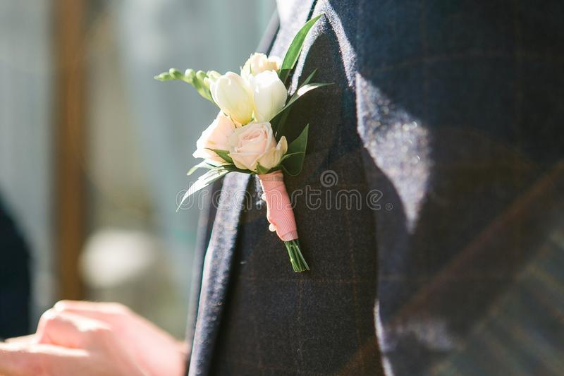 Groom in dark gray suit with a white rose boutonniere. Close up shot in sun beams stock images