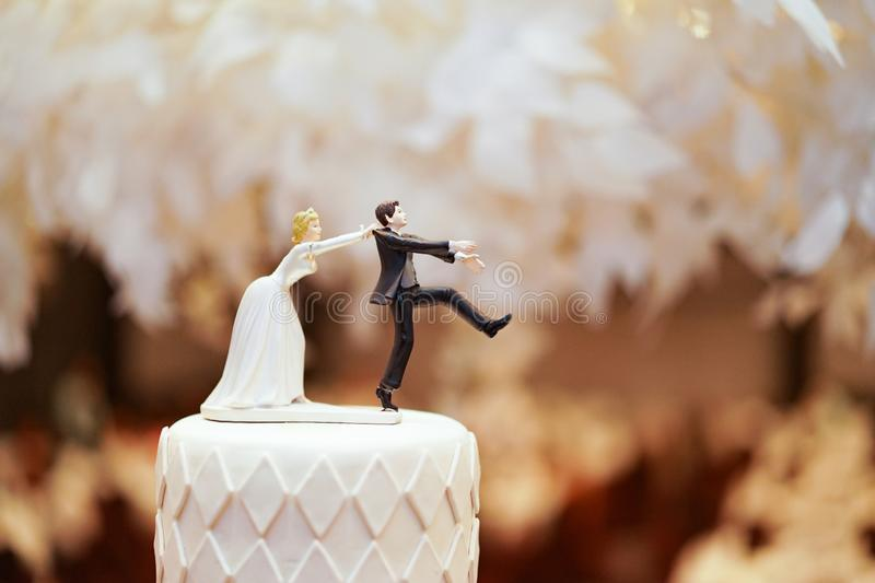 Groom doll and statue is running away but bride can catch him finally. the funny wedding story doll on the top of cake royalty free stock images
