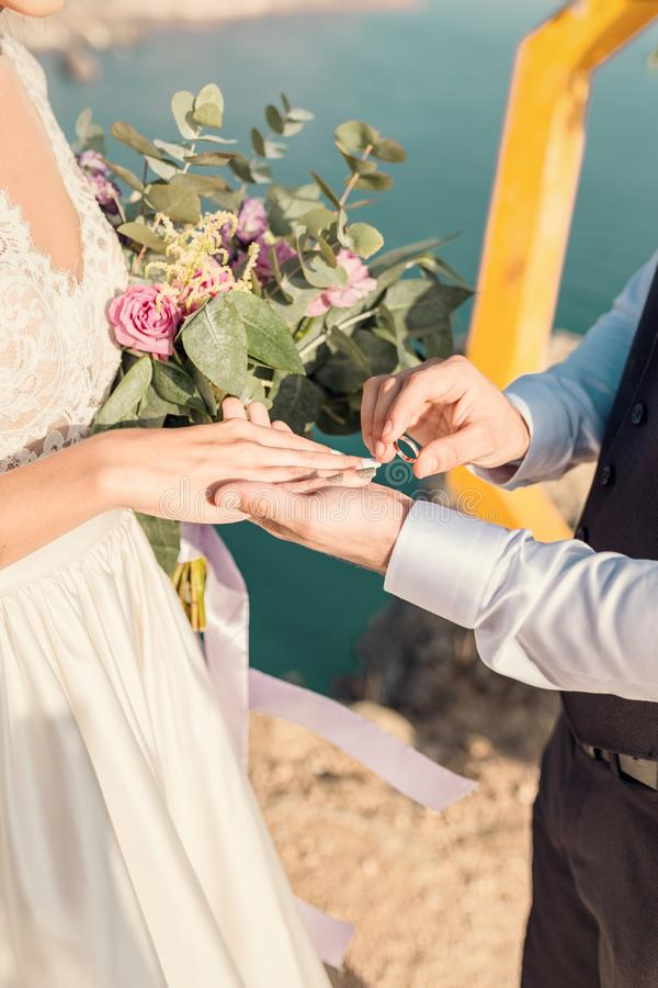 The groom dresses the ring for the bridge at a wedding ceremony on a sea beach. Hands newlywed, close-up royalty free stock photos