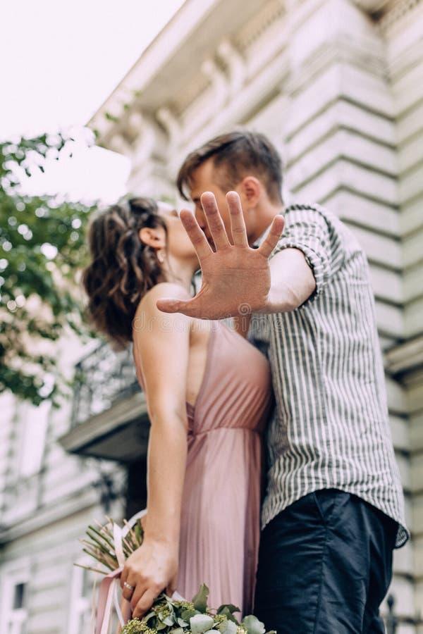 Groom esconde a noiva dos paparazzi Noiva feliz de vestido cor-de-rosa com um buquê de flores e noivo Casal de beijo que se escon fotografia de stock royalty free