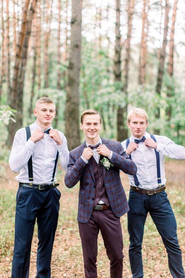 Groom está de pé com seus amigos na madeira do outono Jovem de terno elegante e elegante e cavaleiros em foto de stock royalty free