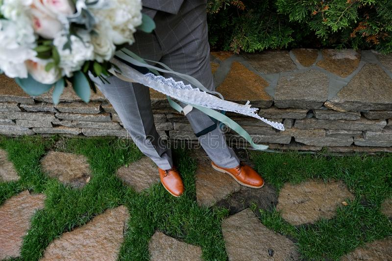 The groom in an expensive luxurious plaid gray suit and leather brown shoes holds a wedding bouquet of roses and leaves, decorated royalty free stock photo