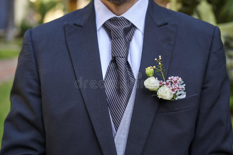 Groom in fancy suit with bouquet waiting for the bride to arrive for wedding ceremony. Groom in fancy suit waiting for the bride to arrive for wedding ceremony royalty free stock photography