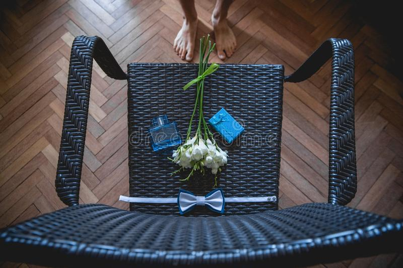 The groom is gathering in the morning. Wedding bouquet, handkerchief butterfly and gift box on the chair. Wedding details. Top stock photo