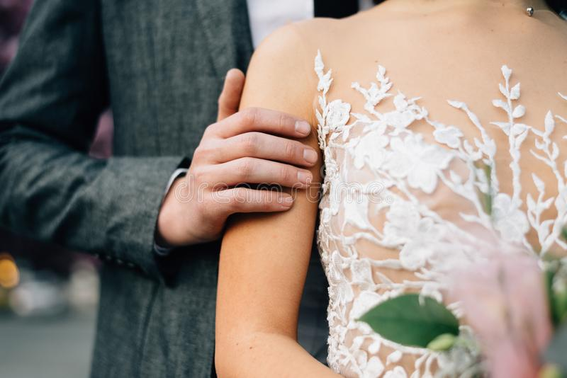 The groom gently strokes the bride. Closeup hands stock photo