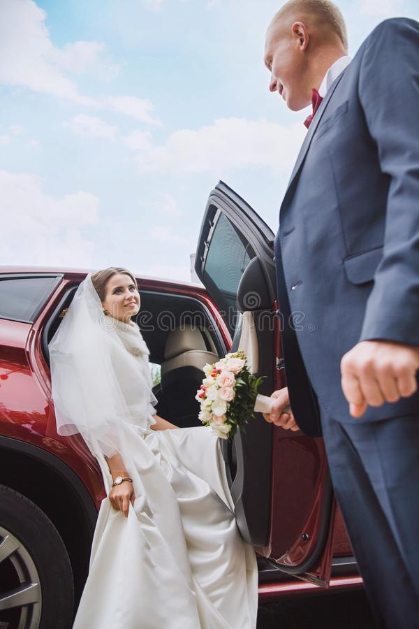 The groom gives hand to the bride. Groom gives hand to bride to get out of car