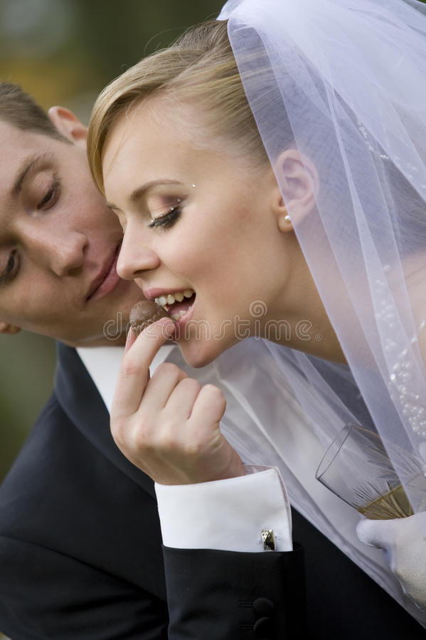 Groom giving bonbon to bride stock images