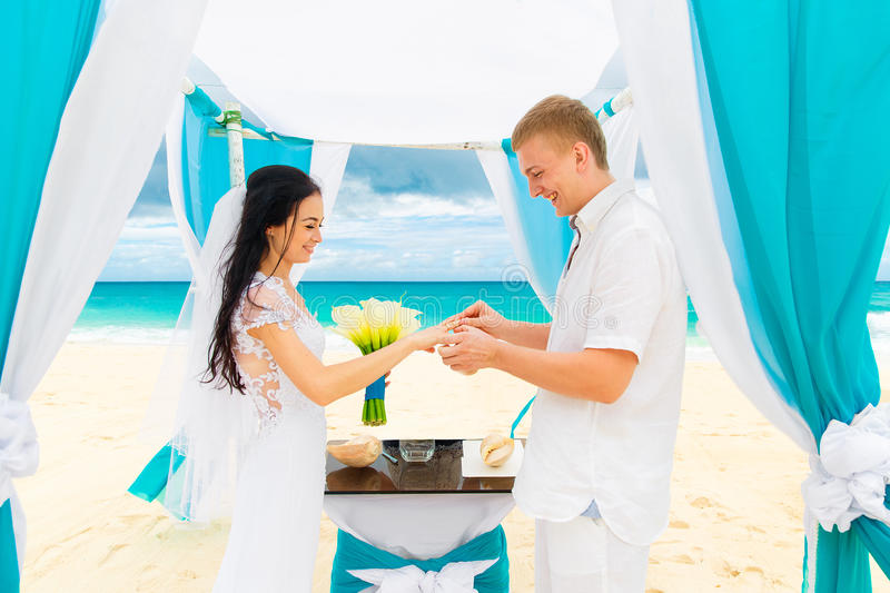 Groom giving an engagement ring to his bride under the arch decorated with flowers on the sandy beach. Wedding ceremony on. A tropical beach in blue. Wedding stock image