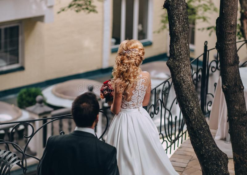 Groom goes bride blonde near railing back stock photos
